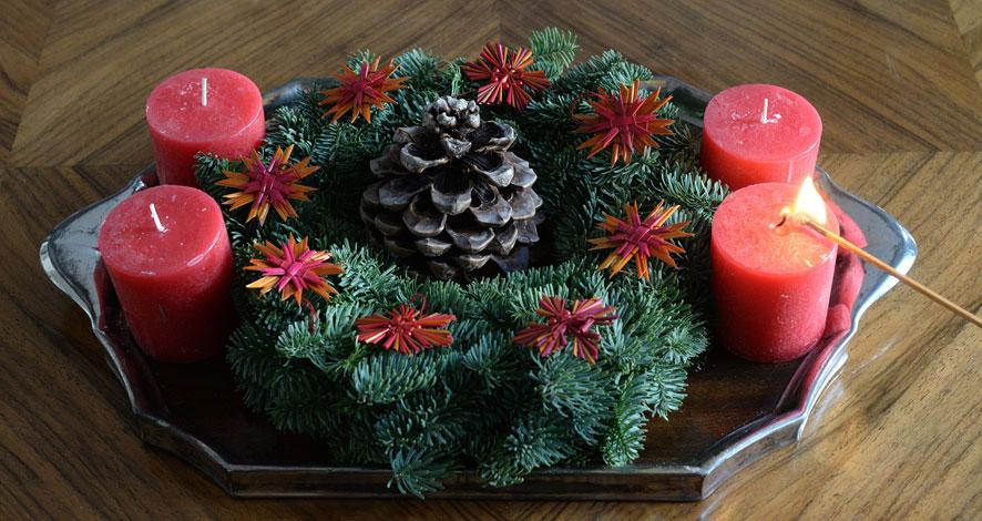 Adventsgesteck mit einer brennenden Kerze