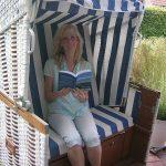 Frau mit Buch im Strandkorb