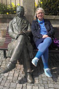 Tibertanz Frau sitzt neben Männerstandbild