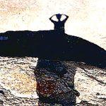 Schatten einer Frau auf hellem Sand