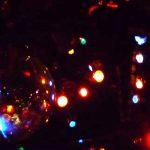 Bunte Lichter spiegeln sich in Christbaumkugeln