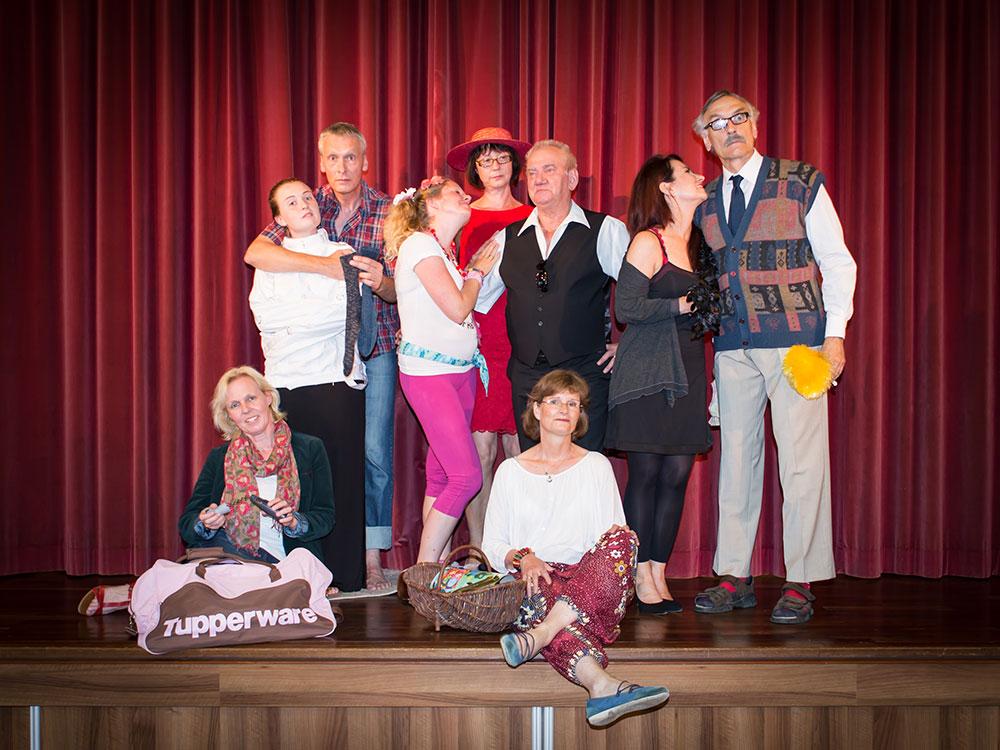 Neun Personen vor einem Bühnenvorhang