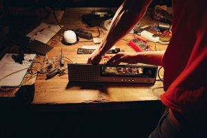 Zwei Hände an einem geöffneten Elektrogerät