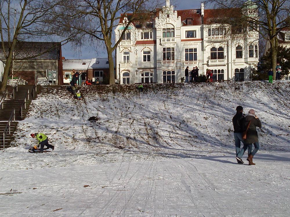 Kinder rodeln an einem kaum verschneiten Deich