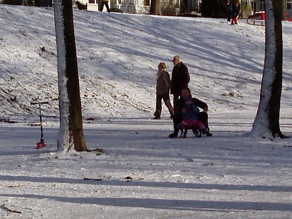Spaziergänger und rodelnde Kinder am Osterdeich