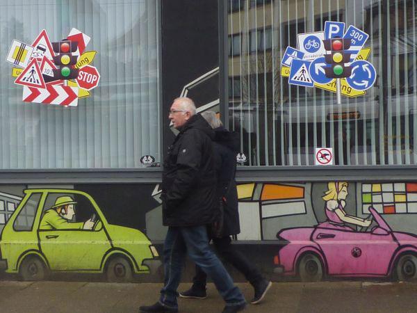 Zwei Personen vor einem Graffiti mit Autos