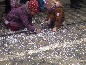 Karneval Bremen, Zwei Mädchen sammeln Konfetti von der Straße auf