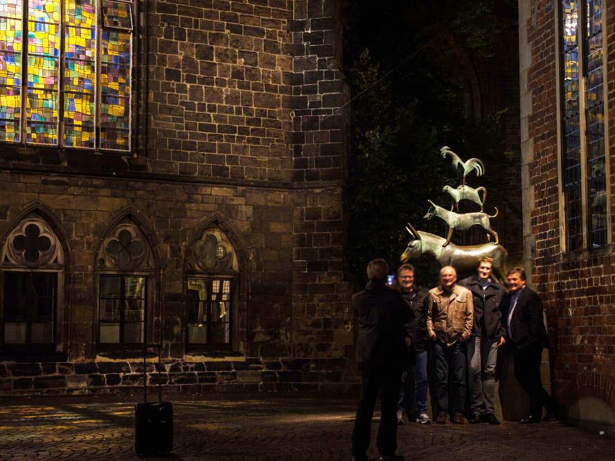 Fünf Männer vor der Skulptur der Stadtmusikanten bei Nacht.