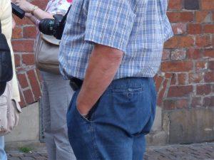 Männertorso mit Kamera vor dem Bauch und Hand in der Hosentasche