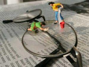 Miniaturfiguiren putzen eine Brille