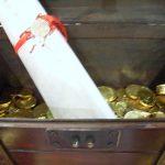 Schatz, Geöffnete Schatztruhe mit Geldstücken und Schatzkarte