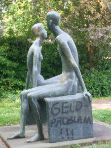 """Skulptur, Mann und Frau, mit Aufschrifft """"Geldproblem"""""""