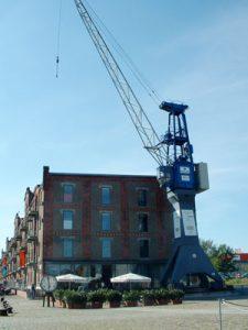 blauer Kran vor Speichergebäude Gebäude
