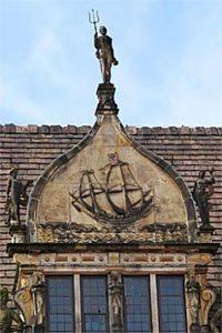 Poseidon, Steinfigur mit Dreizack auf einem mittelalterlichen Giebel