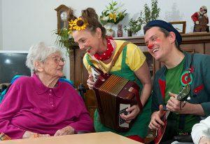 Zwei Clowns machen Musik und eine alte Dame freut sich darüber