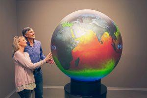 Zwei Personen an einem großen Globus