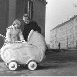 Zwei Mädchen hinter einem Babywagen der 50ger Jahre