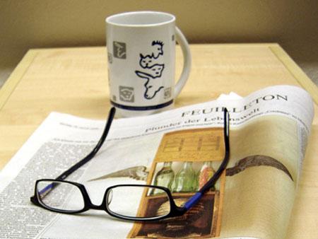 Unwort, Zeitung mit Brille und Kaffeetasse
