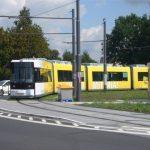 Eine gelbe Straßenbahn in der Kurve