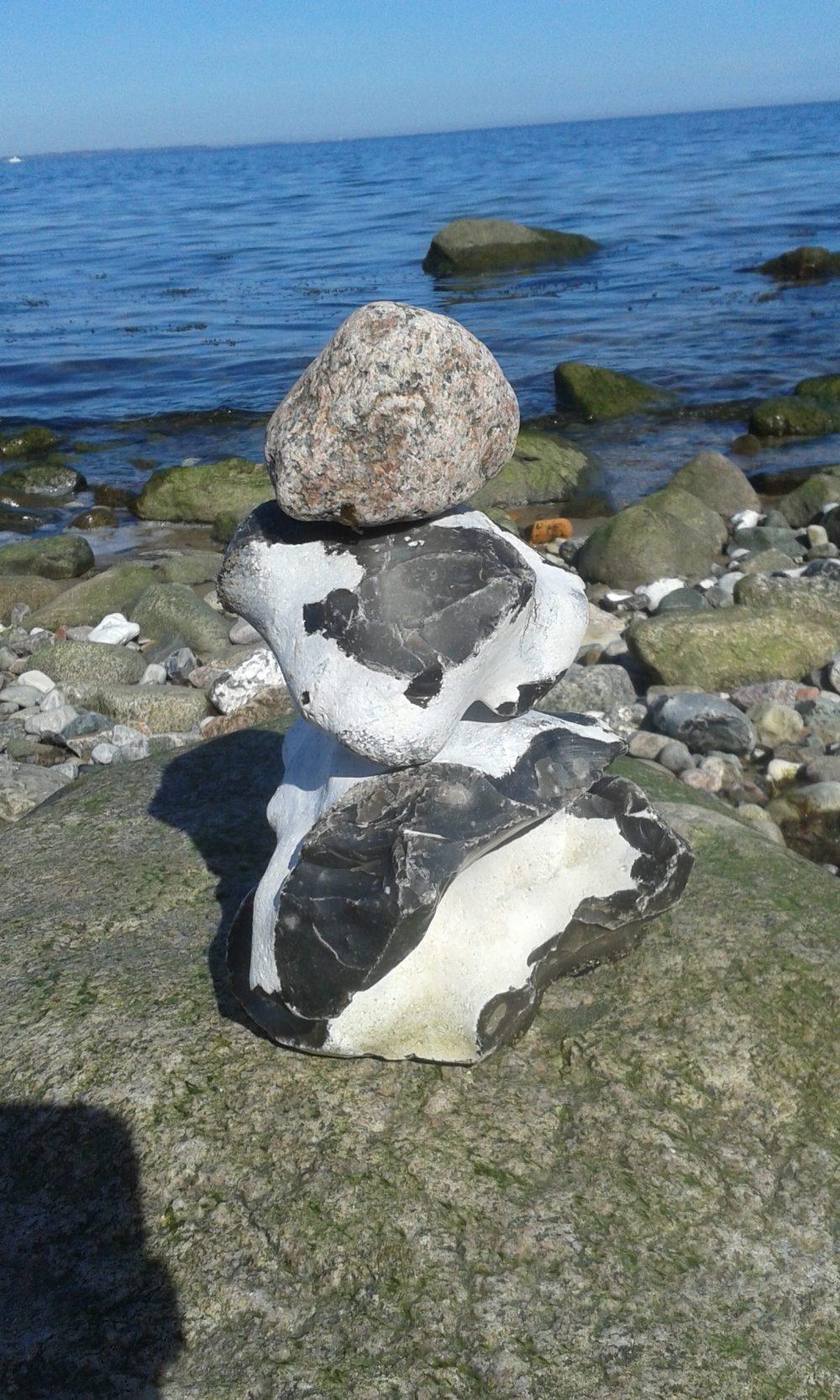 Aufgeschichtete Steine. Im Hintergrund das blaue Meer