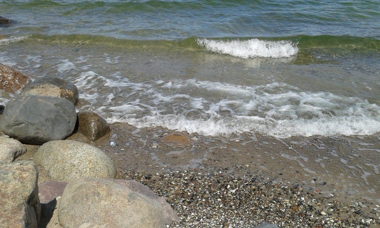 Leichte Wellen am Strand mit Steinen