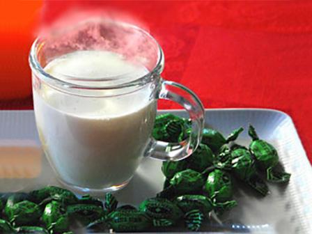 Hausmittel, Glas mit heißer Milch auf einem Tablett mit Hustenbonbons
