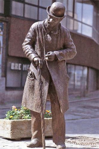Bronzefigur eines Mannes mit Hut und Zigarre