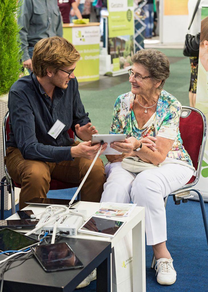 Seniorenmesse, Junger Mann und alte Dame im Gespräch