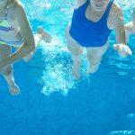 Eine Frau und zwei Mädchen aus der Unterwasserperspektive in einem Schwimmbad fotografiert.