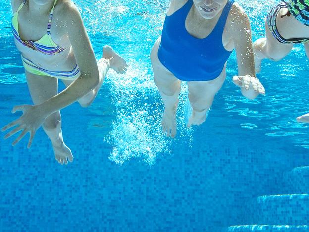 Schwimmbad, Eine Frau und zwei Mädchen aus der Unterwasserperspektive in einem Schwimmbad fotografiert.
