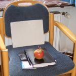 Platz besetzen, Stuhl mit Apfel und Schreibutensilien besetzt.