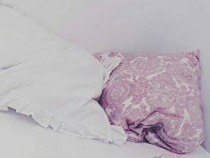 Zwei Kissen liegen verknautscht nebeneinander auf einer Matratze. Das auf der linken Seite hat einen weißen Bezug mit Rüschen. Das Rechte hat ein rötlich-weißes Muster.