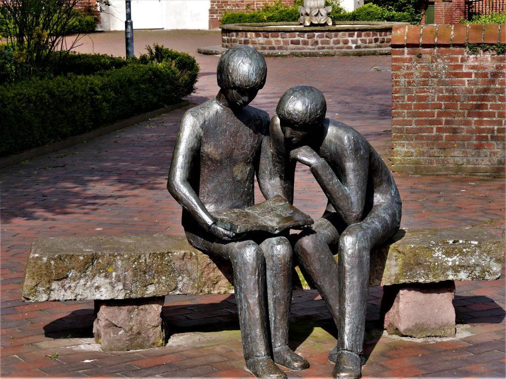 Skulptur zweier gemeinsam lesender Menschen