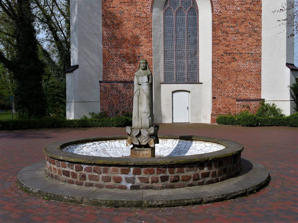 Runder Brunnen aus Backsten mit einer Frauenskulptur im Zentrum