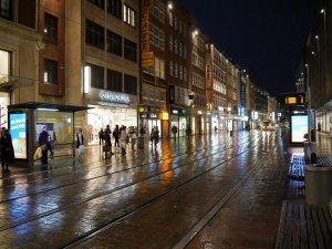 Dunkelheit, Ladenbeleuchtung spiegelt sich auf nasser Fahrbahn