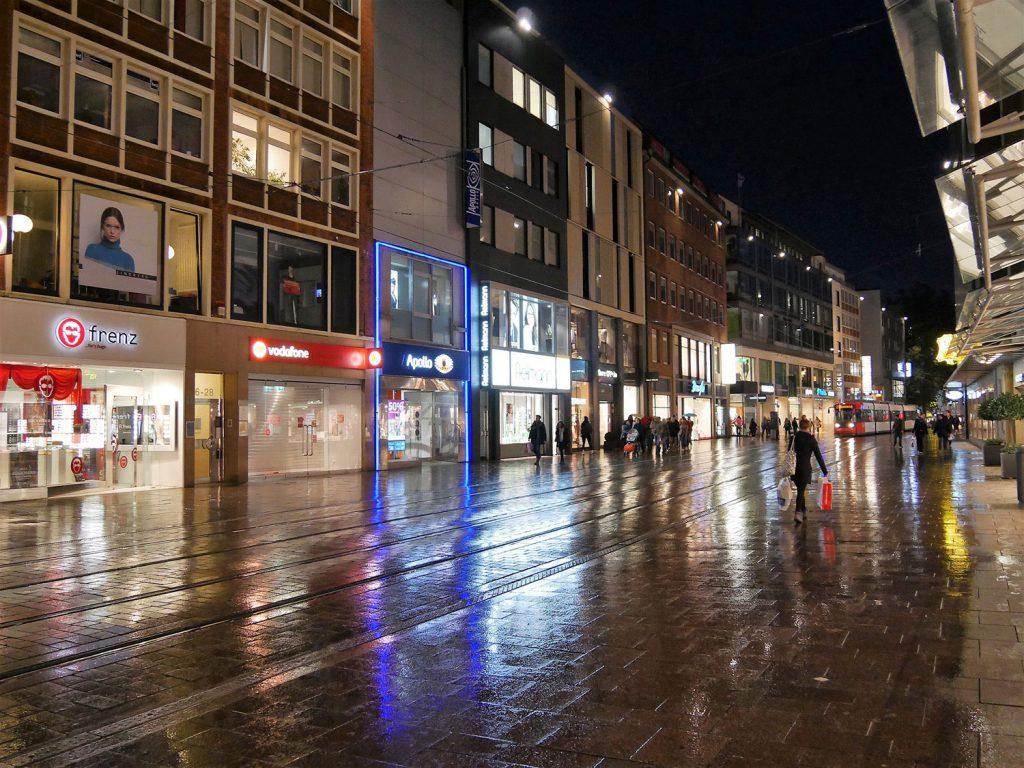 Ladenbeleuchtung spiegelt sich auf nasser Fahrbahn