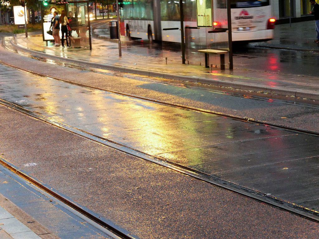 November, Straßenlichter spiegeln sich auf nassem Asphalt zwischen Schienen