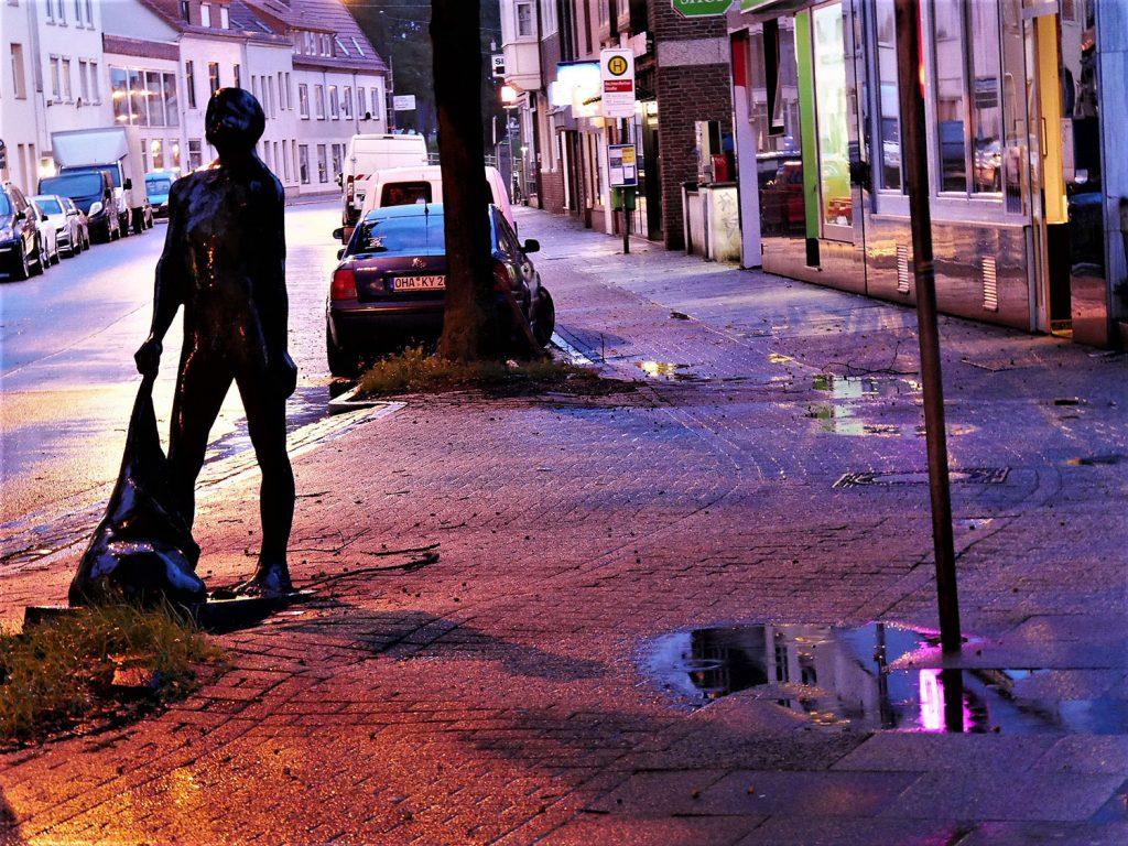 November, Skulptur eines Mannes mit einem Laubsack