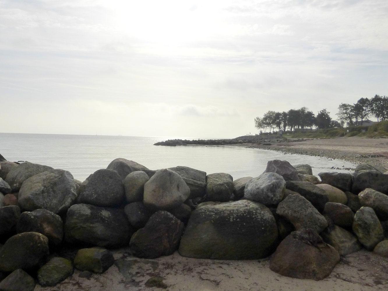 Sonne über einer Bucht ,it Strand und einem Haufen Feldsteine