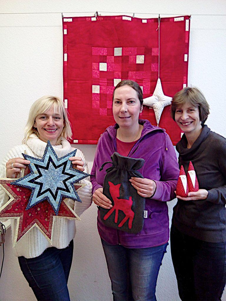 Nähwerkstatt, Drei Frauen halten genähre Produkte, Sterne, Wärmflaschenhülle und Wichtel