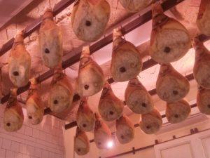 Fleischkonsum, Viele Schinken hängen an einer Decke