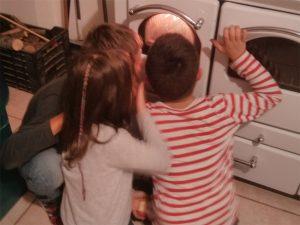 Drei Kinder betrachten ein Feuer im Ofen