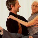 Junger Mann tanzt mit alter Frau