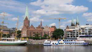 Groß-Segler und Ausflugsdampfer vor einer Backsteinkirche