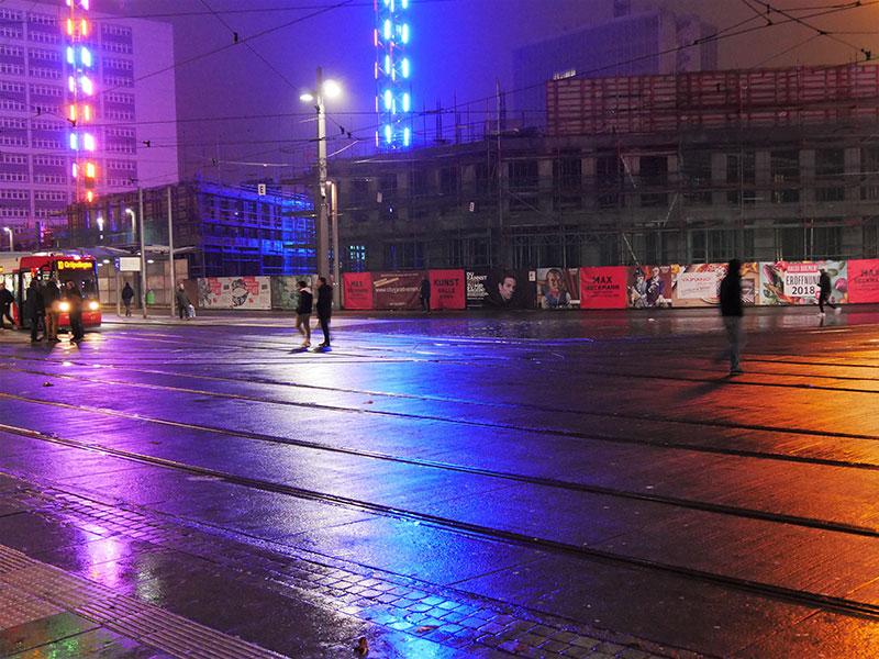 Bunte Lichter an mehreren Baukränen, davor Straßenbahnschienen