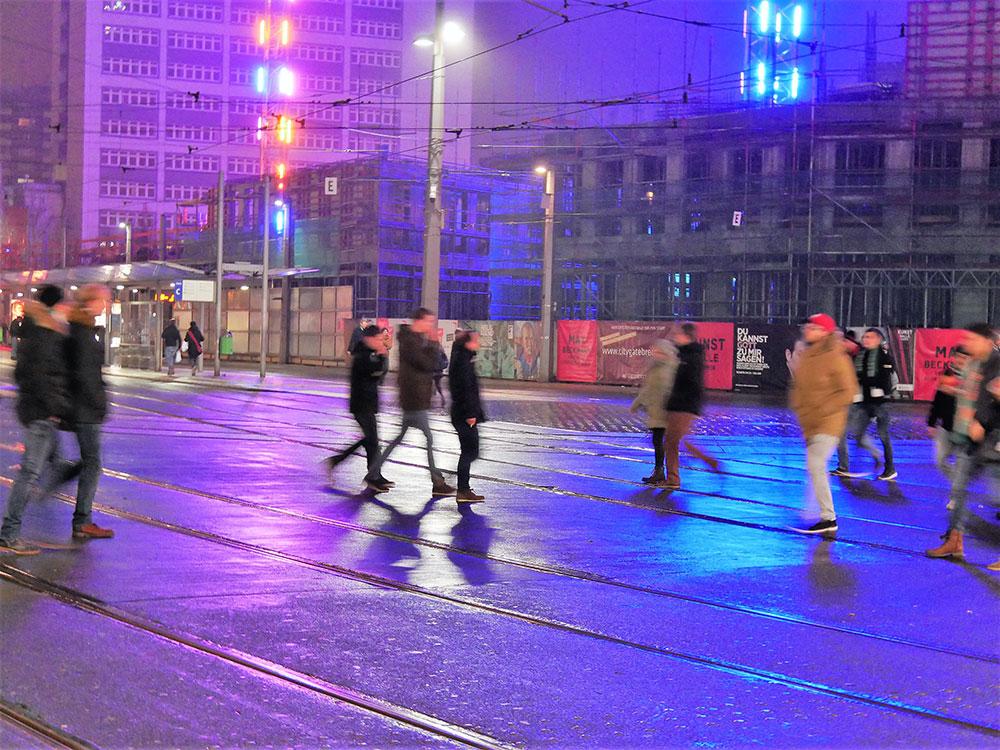 Bunte Lichter an mehreren Baukränen, davor Straßenbahnschienen und Menschen
