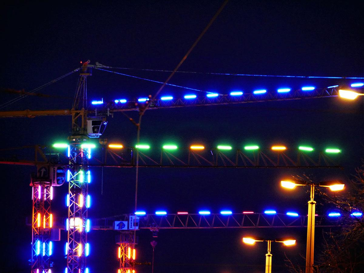 Bunte Lichter an mehreren Baukränen