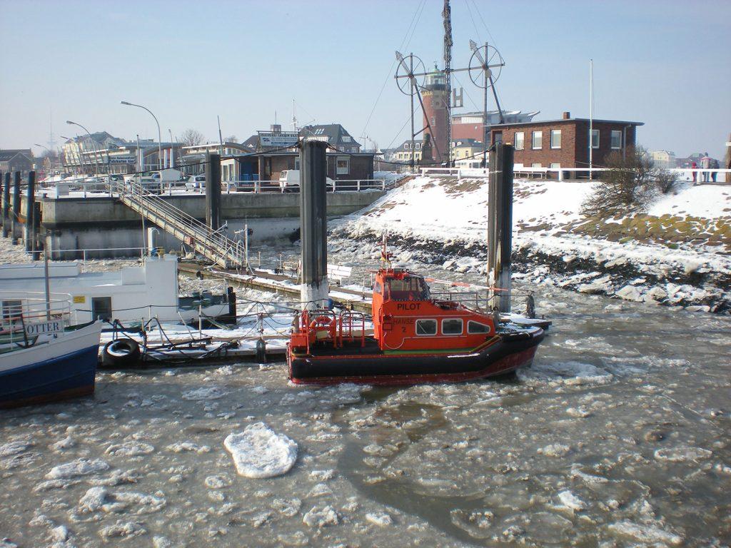 Hafenbecken mit Eisschollen und rotem Boot