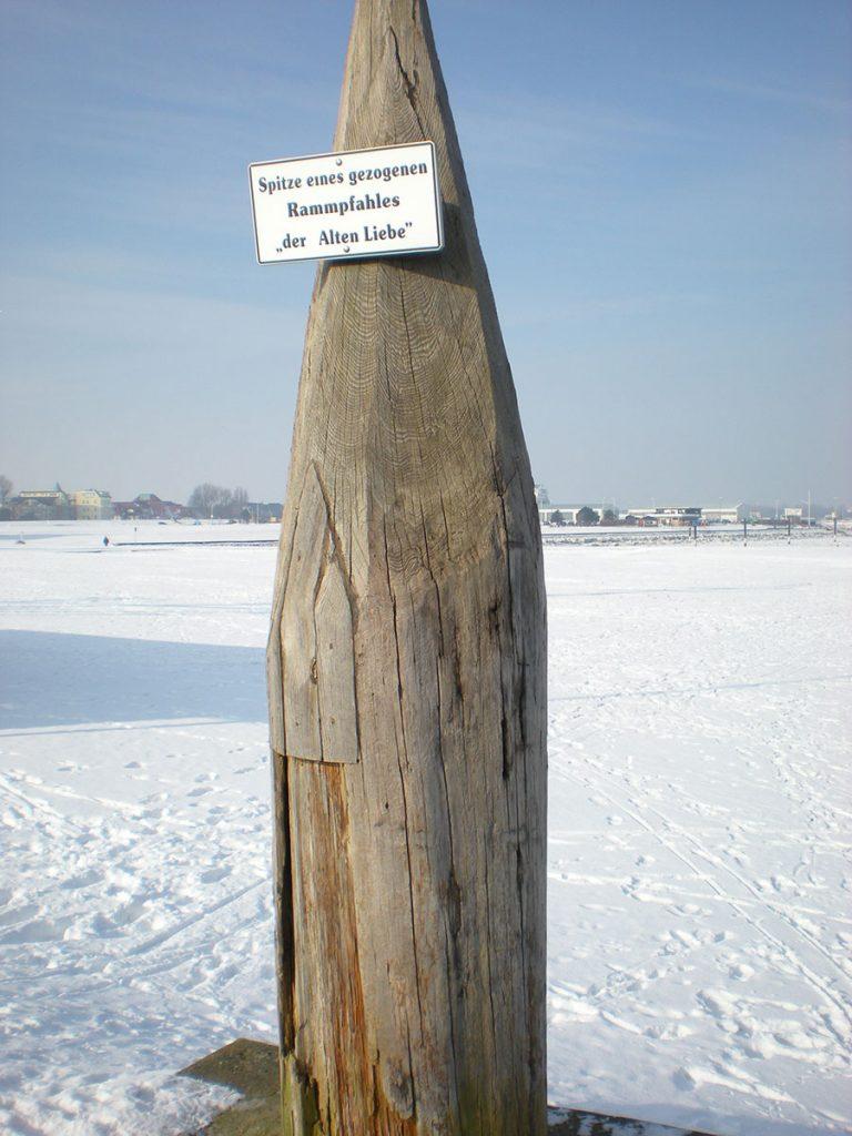 Hölzerner Rammpfahl steht in gefrorenem Boden