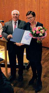 Zwei Personen mit Urkunde und Blumenstrauss